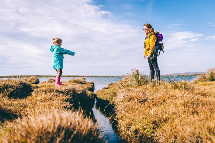 Madre e hijo en saltando un obstáculo en la montaña gracias a la comunicacion y la confianza. Dened